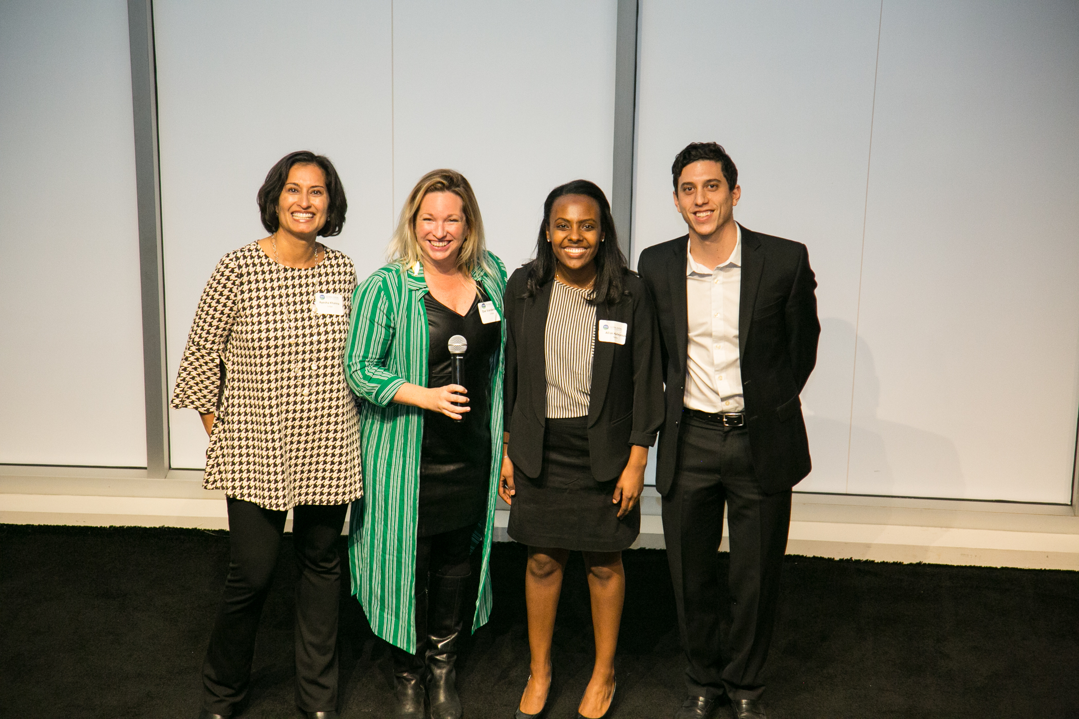 Global Finalist team, NeMo (Johns Hopkins), on stage with judges Ayesha Khanna (Points of Light) and Dar Vanderbeck (CARE)