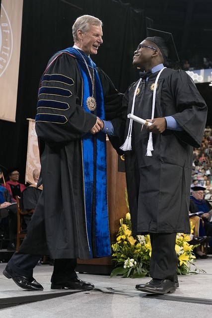 President Bud Peterson congratulates an undergraduate at the Saturday afternoon ceremony.