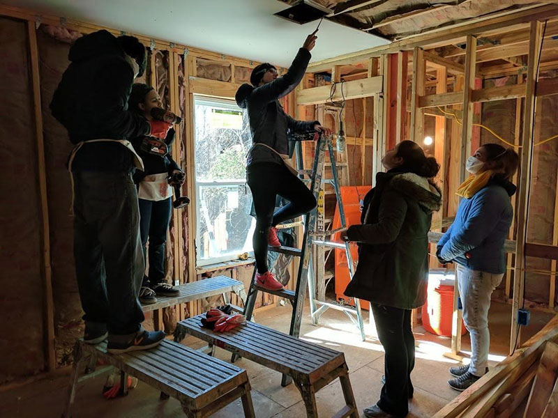 MBA students insulated a newly built home and installed ceiling, floor, and bathroom drywall